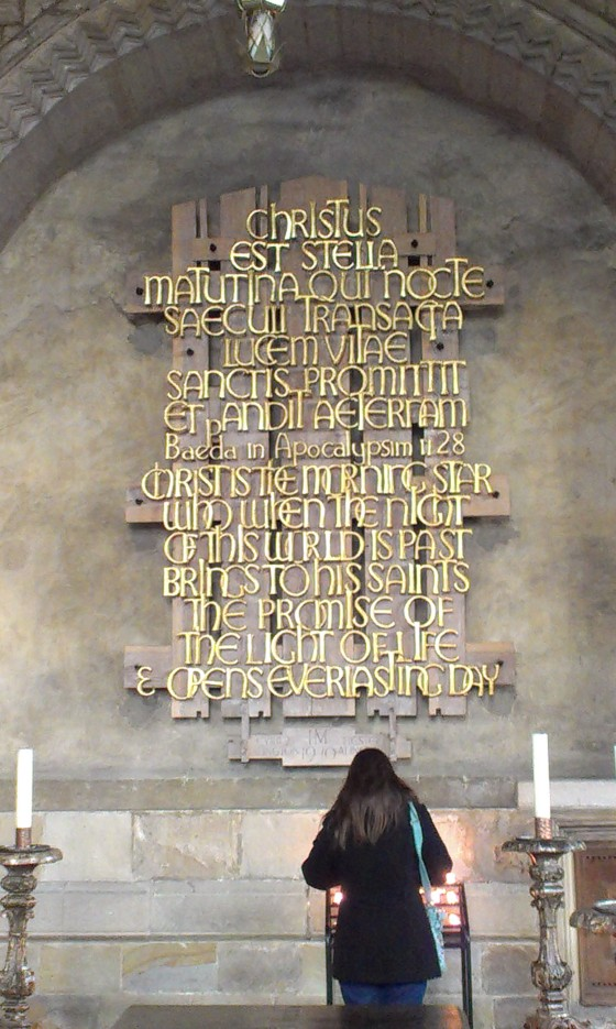 I light candles beneath the inscription.